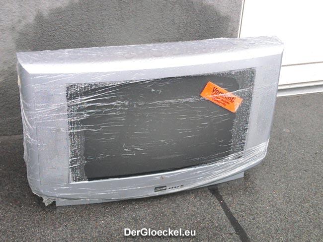 am Gehsteig zwischengeparkter Fernseher