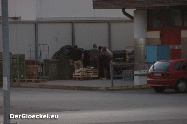 Menschen durchstöbern Mülltonnen eines Supermarktes nach Lebensmitteln